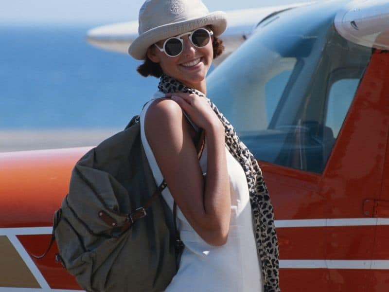 Girl with eco friendly personal item bag in front of airplane