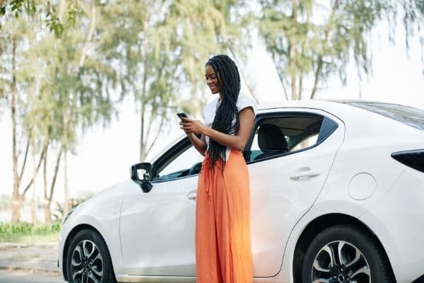 Woman texting outside her car is a way to stop idling your car