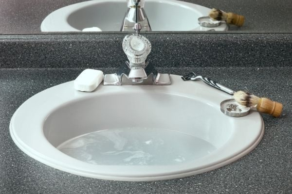 Bathroom sink with water and shaving kit