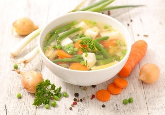 Bowl of veggie soup surrounded by veggies