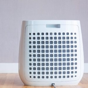 Air purifier on floor by purple wall