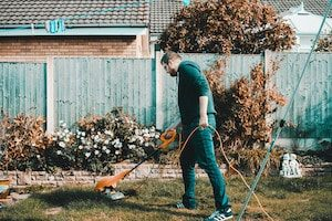 Man Holding Orange Electric Grass Cutter on Lawn