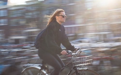 Bicyclist riding through town is Reducing Air Pollution from Vehicles