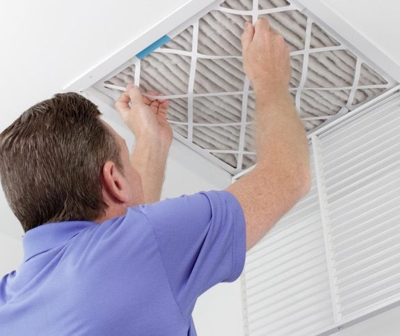 Man installing HVAC air filter to reduce indoor air pollution