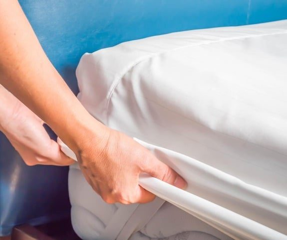 Person changing sheets on bed to reduce indoor air pollution